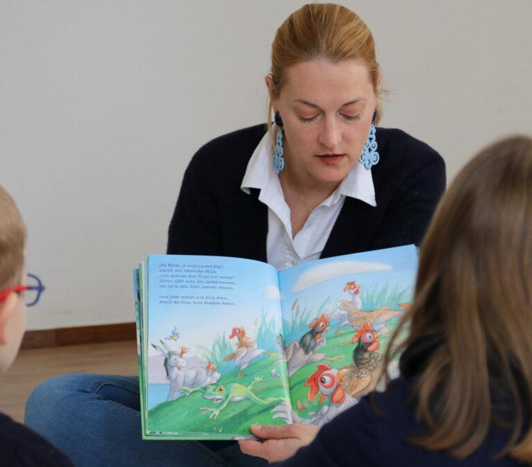 Julia zeigt den Kindern das Kinderbuch, während sie weiter vorliest.