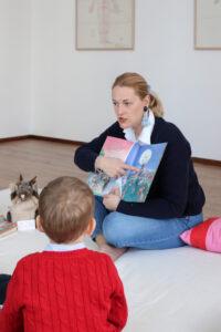 Julia zeigt den Kindern, die vor ihr sitzen eine Stelle im Buch.