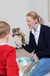 Julia zeigt Kindern das Maskottchen, eine Ratte mit Rucksack.